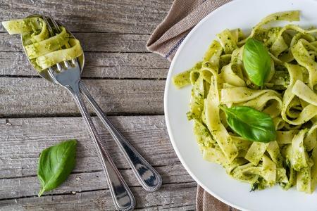 Pesto pasta op een witte plaat, bovenaanzicht, rustieke houten achtergrond