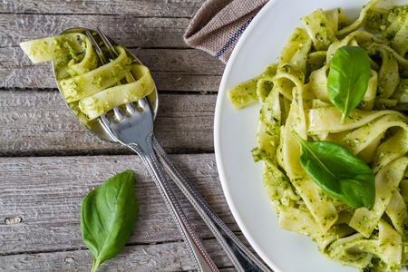healthy lunch: Pesto pasta on white plate, top view, rustic wood background Stock Photo