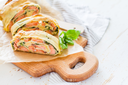 strudel: Salmon and spinach strudel on white wood background Stock Photo