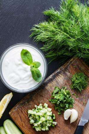 Preparing tzatziki sauce and ingredients, dark stone background, top view