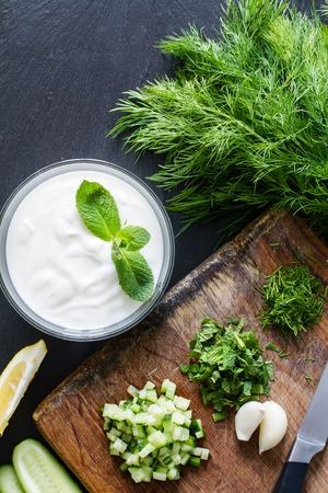 yaourt: Préparation de la sauce et les ingrédients tzatziki, fond sombre de la pierre, vue de dessus