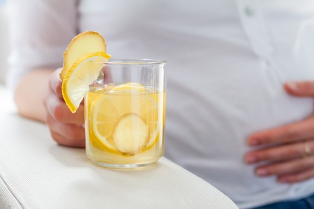 fruit in water: Pregnant female holding ginger tea in glass cup, closeup