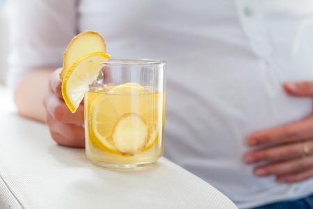 Schwangere Frauen halten Ingwer Tee im Glas, Nahaufnahme Standard-Bild