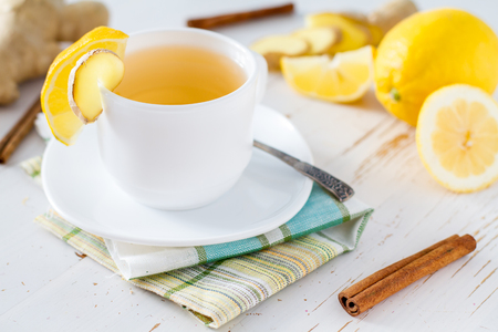 brown white: Ginger lemon cinnamon tea, white wood background