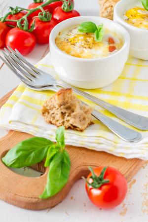 ramekin: Egg cocotte  in white ramekin with tomato and basil, white background Stock Photo