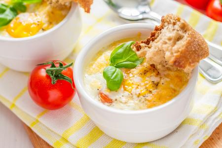 ramekin: Egg cocotte  in white ramekin with tomato and basil, closeup