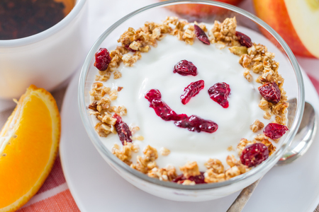 breakfast food: Granola and yogurt with smile face ,white wood background