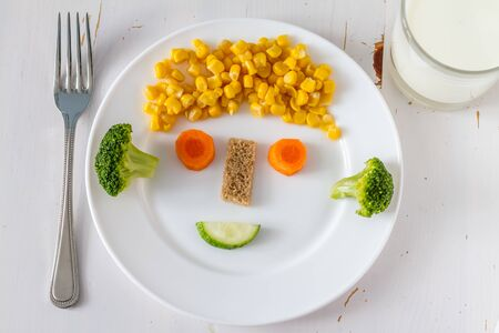 fresh vegetable: Fruits and vegetables arranged to look appealing to kids in funny face, white plate