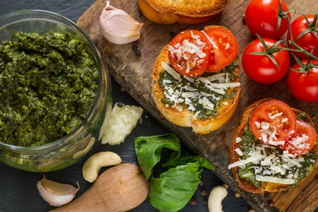 sause: Toasts with pesto sause and tomatoes, closeup