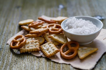 salty: Selection of salty snacks, wood background, closeup Stock Photo