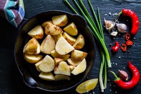 raw potato: Raw potato slices with herbs, spices, dark stone background Stock Photo