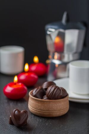 candles in the dark: Chocolate candies with coffee and candles, dark stone background