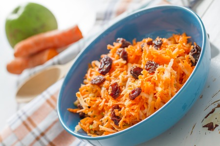 ensalada: Carrot salad with raisins and apple in blue bowl