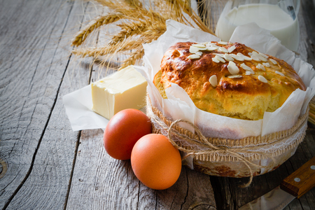 Easter bread and ingredients on rustic wood background, copy space