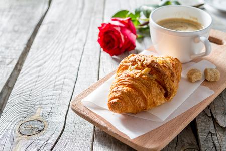 Valentinstagfrühstück - köstliche frische Hörnchen mit Kaffee und stieg, Kopienraum