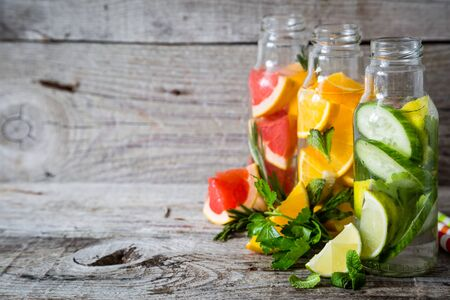 infusing: Selection of infused water in glass bottles, rustic wood background, copy space