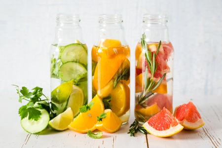 infusing: Selection of infused water in glass bottles, white wood wood background, copy space