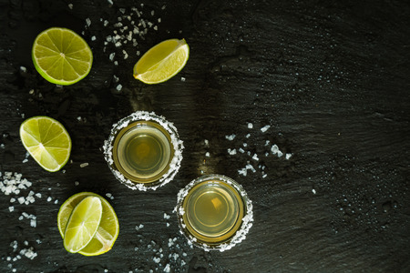 Gold tequila shots on rustic wood background, copy space Stock Photo