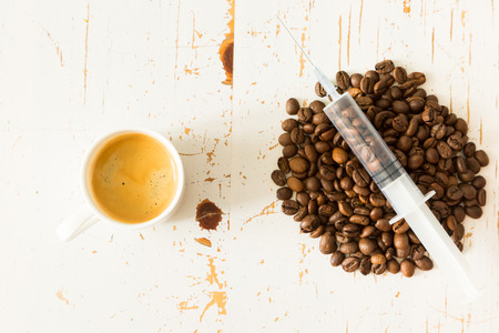addictive drinking: Health care concept - coffee beans in plastic syringe, white background, copy space Stock Photo