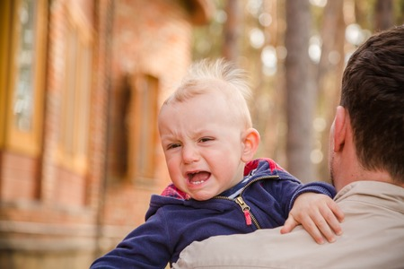 colic: Baby boy crying on his father shoulder, copy space Stock Photo