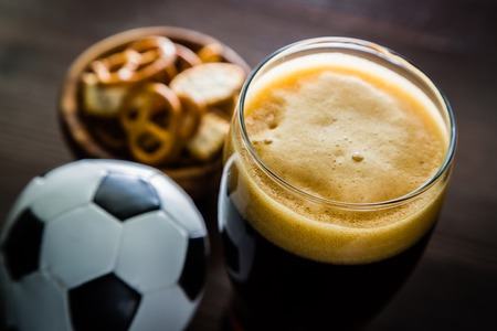 pouring beer: Pouring beer into glass with snacks and football, closeup Stock Photo