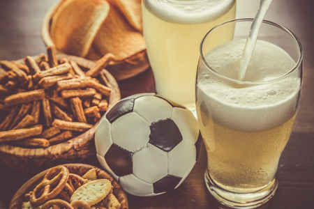 pouring beer: Pouring beer into glass with snacks and football, toned