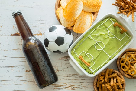 themed: Selection of party food for watching football championship, soccer field dip, top view