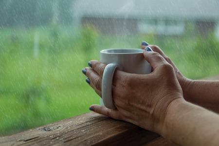 Weibliche Hände Tasse Kaffee in den regnerischen Tag halten, Kopier-Raum