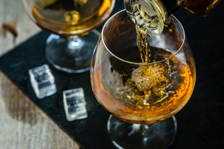 cognac: Pouring cognac in a glass, rustic background