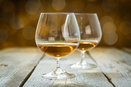 cognac: Cognac in glasses on rustic background with bokeh at background