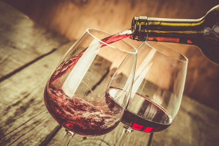 Pouring wine in a glass, copy space, toned Stock Photo
