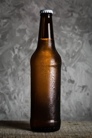 Beer in bottle with ice drops, rustic background Stock Photo