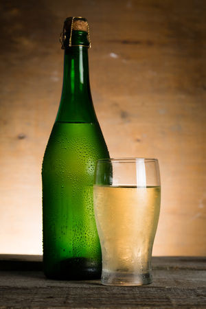 Apple cider in glass bottle with water drops, copy space Stock Photo