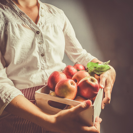 Female holding apple box, copy space, toned Stock Photo