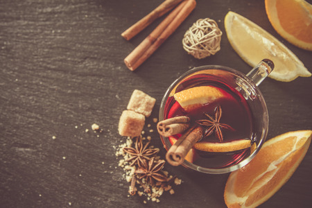 punch spice: Mulled wine ingredients on dark stone background, top view, toned