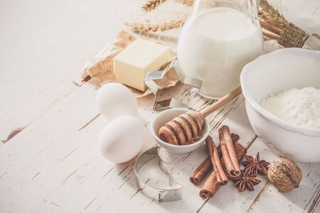 Ingredients for baking - milk butter eggs flour wheat, white wood background, copy space, toned
