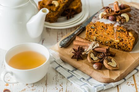 Spicy carrot cake with nuts on wood background