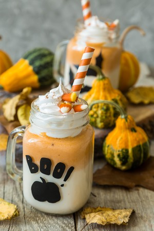 Halloween style pumpkin spice latte in glass jar, copy space