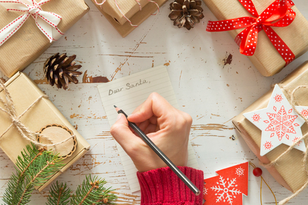 wishlist: Making list of presents on wood background, copy space