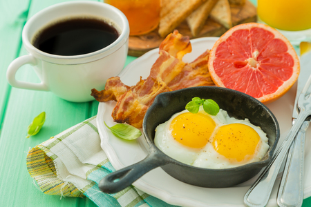eggs and bacon: Summer breakfast - eggs, bacon, toast, jam coffee juice copy space