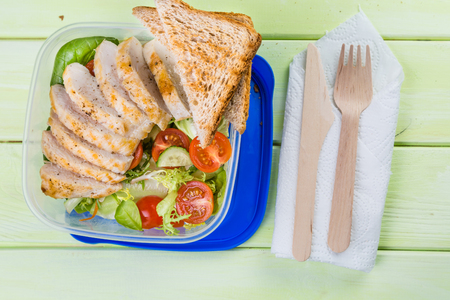 boxed: Lunch box with salad and chicken, top view Stock Photo