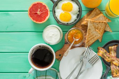 Summer breakfast - eggs, bacon, toast, jam coffee juice copy space