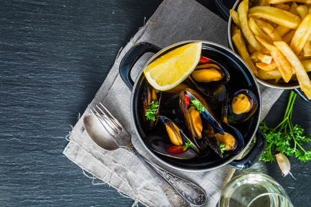 Mussels in pan on rustic background