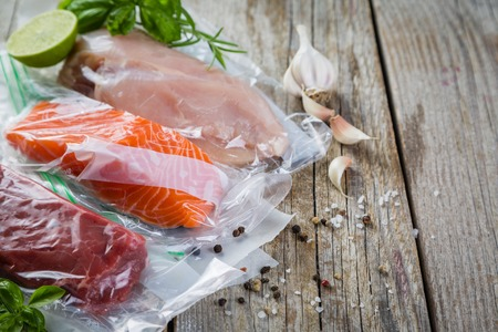 Beef, chicken and salmon in vacuum plastic bag for sous vide cooking Imagens