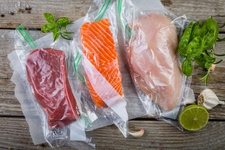 Beef, chicken and salmon in vacuum plastic bag for sous vide cooking Archivio Fotografico