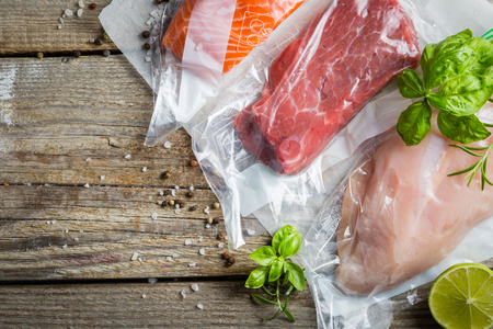 Beef, chicken and salmon in vacuum plastic bag for sous vide cooking Standard-Bild