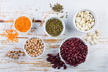 Selection of colorful beans on white wood background Stock Photo