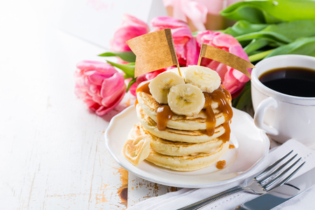 Mothers day breakfast concept - pancakes, coffee, flowers, present Stock Photo