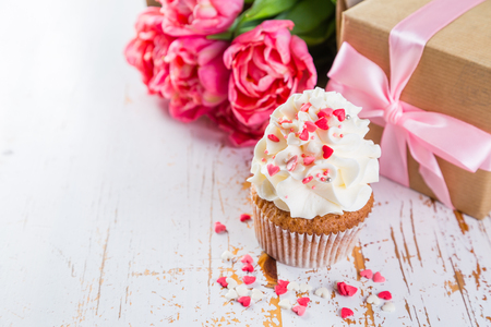 Cupcakes with vanilla frosting and hearts with coffee and present