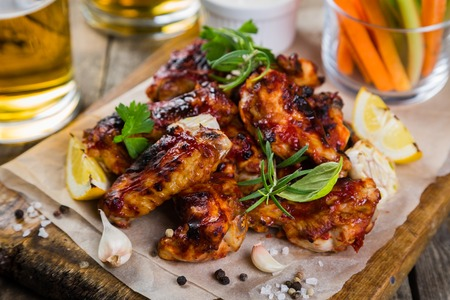 jerk: Chicken wings on wood board with beer and vegetable sticks